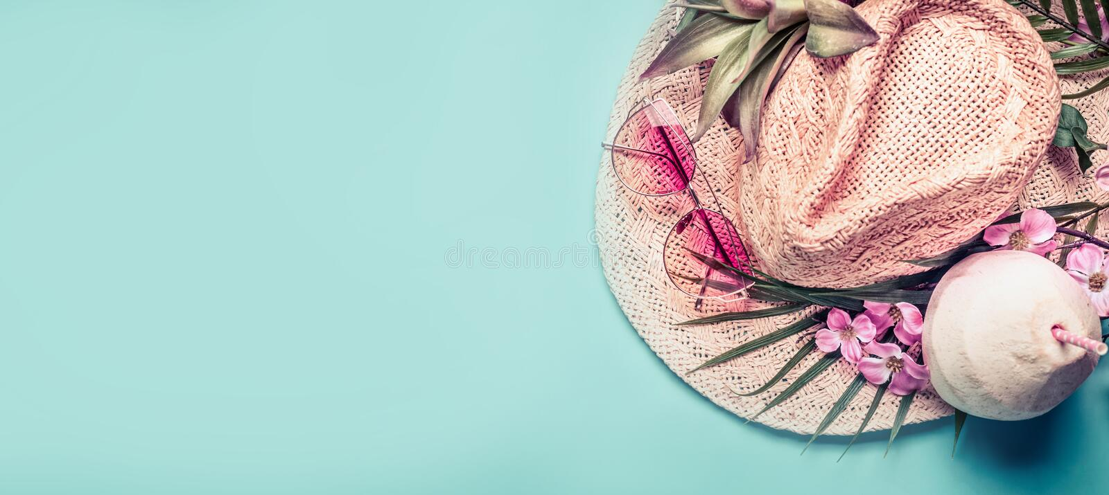 Summer holiday banner. Beach accessories : straw hat, palm leaves, pink sun glasses, flowers and coconut cocktail on blue turquoi royalty free stock photo