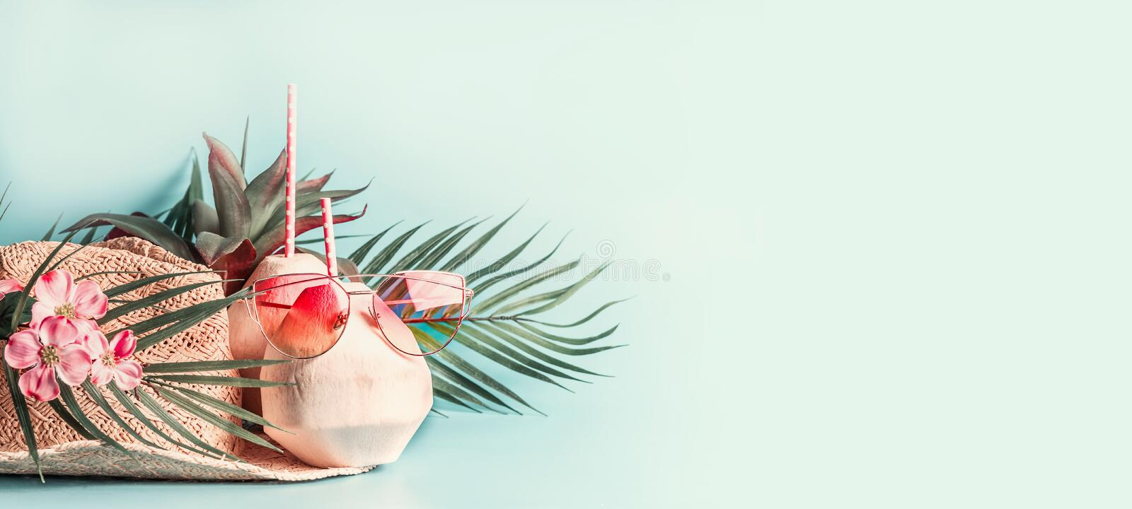 Summer holiday . Beach accessories : straw hat with palm leaves and flowers, pink sun glasses and coconut cocktail on blue turquo royalty free stock photography