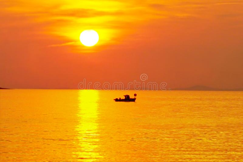 Summer holiday with big yellow sun and fishing boat silhouette at sunset. Summer sunset in orange color tone nature background with big yellow sun and black stock photos