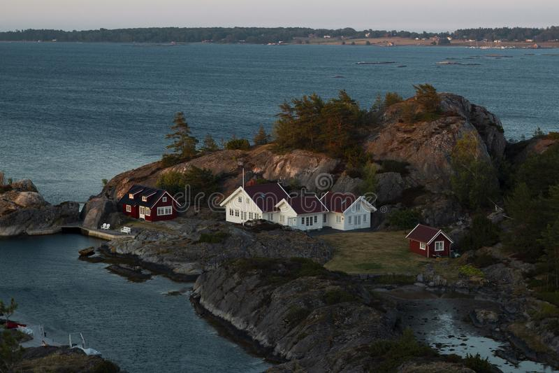 Cabins on Remote Norwegian Island. Summer holiday cabins on the islands of kragerø in Norway. Taken at approximately 10pm as dusk nears stock images