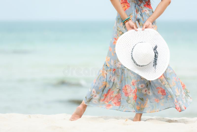 Summer Holiday. Close up hand holding big white hat.  Lifestyle woman wearing fashion summer trips standing on the sandy ocean bea. Ch. Happy woman enjoy and stock photography