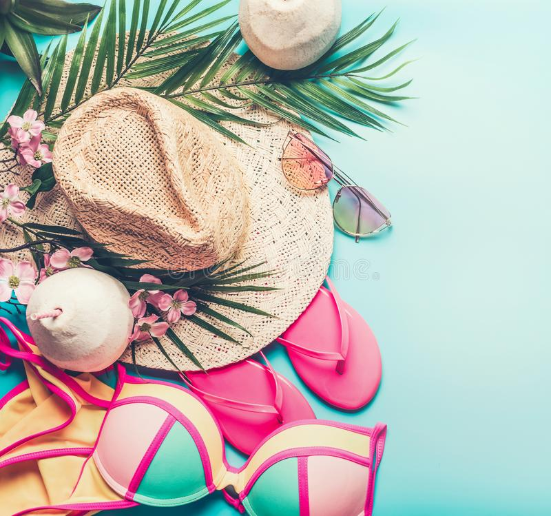 Summer holiday concept. Beach accessories : straw hat, palm leaves, sun glasses, pink flip flops , bikini and coconut cocktail royalty free stock photo