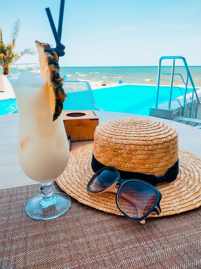 Summer holiday concept with cocktail and sun protection,sunscreen,hat by the pool and blur beach on background stock photography