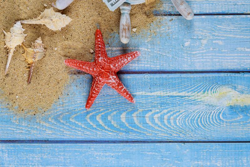 Summer holiday concept, seashells, starfish on beach sand of dollar banknote. A wooden boards stock images
