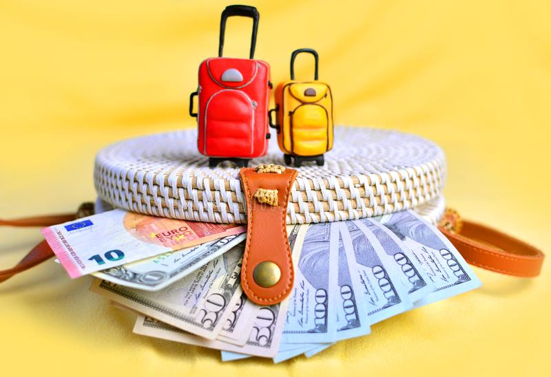 Summer holiday concept with small women`s handbag, miniature travel suitcases and money stock image