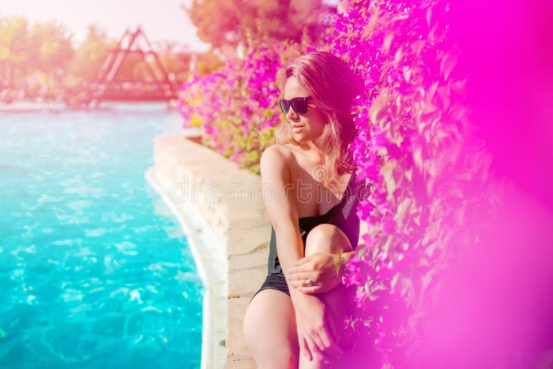 Summer holiday - suntanned sexy caucasian woman relaxing near swimming pool, poolside with straw hat and sunglasses royalty free stock photography
