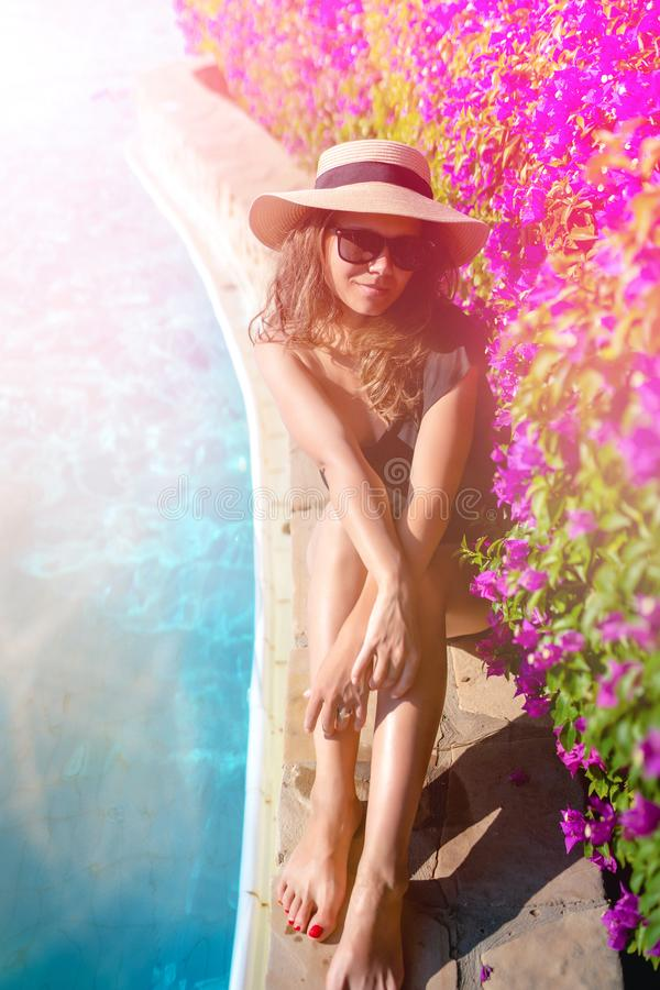 Summer holiday - suntanned sexy woman relaxing near swimming pool, poolside with straw hat and sunglasses stock photography