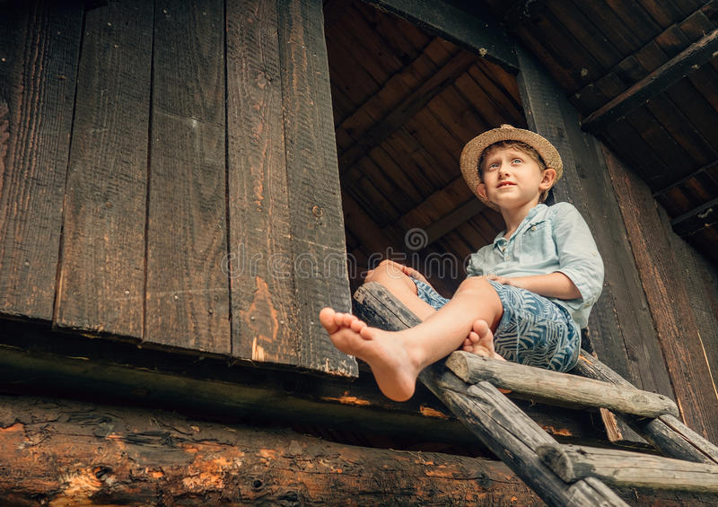 Summer holiday in countrysiade. Boy sits on the wood leader to barn stock photo