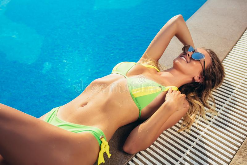 Suntanned young woman relaxing near swimming pool stock photography