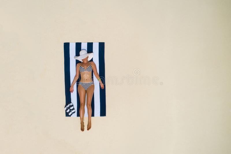 Summer holiday fashion concept - tanning girl wearing sun hat at the beach on a white sand shot from above.Top view from drone. Aerial view of slim woman stock image