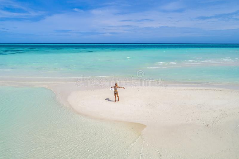 Summer holiday fashion concept - tanning girl wearing sun hat at the beach on a white sand shot from above.Top view from drone. Aerial view of slim woman royalty free stock images