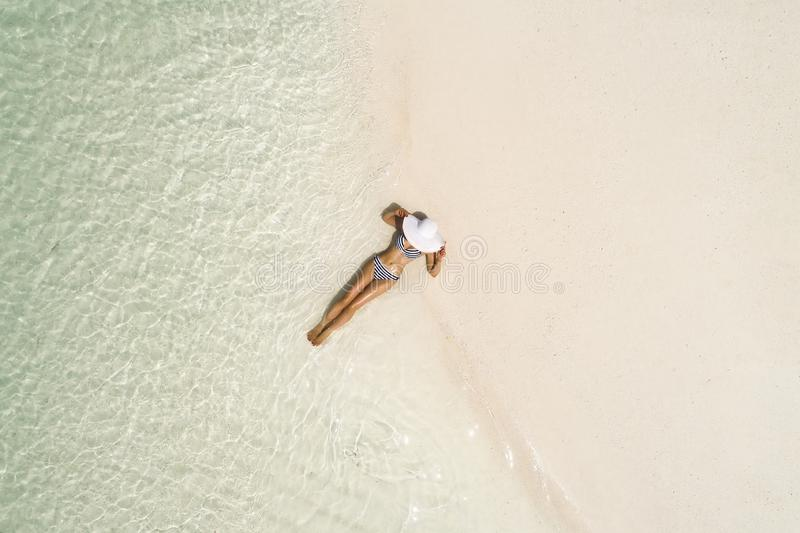 Summer holiday fashion concept - tanning girl wearing sun hat at the beach on a white sand shot from above.Top view from drone. Aerial view of slim woman royalty free stock photography