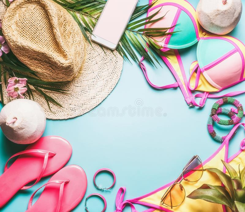 Summer holiday frame. Beach accessories : straw hat, palm leaves, sun glasses, pink flip flops , bikini and coconut cocktail stock photos