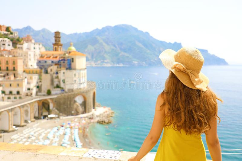 Summer holiday in Italy. Back view of young woman with straw hat and yellow dress with Atrani village on the background stock images