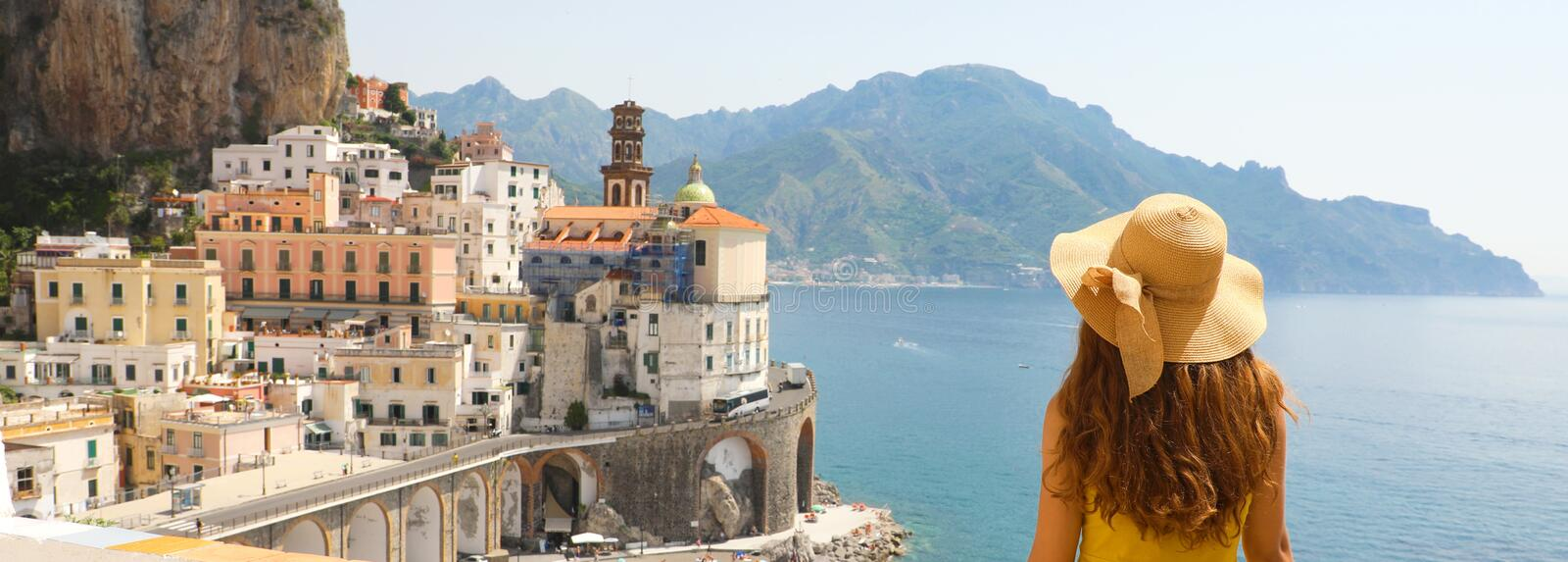 Summer holiday in Italy panorama banner. Back view of young woman with straw hat and yellow dress with Atrani village royalty free stock images