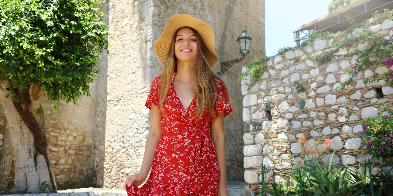 Summer holiday in Italy. Portrait of young woman with straw hat and red dress walking in sicilian village of Taormina, Italy royalty free stock photo