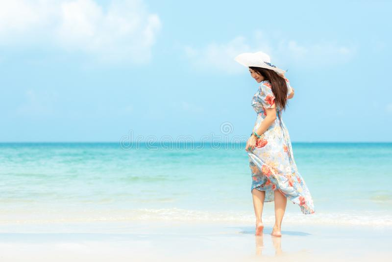 Summer Holiday.  Lifestyle smiling asian woman wearing dress fashion summer trips relax on the sandy ocean beach. royalty free stock photos