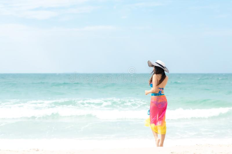 Summer Holiday. Lifestyle woman chill holding big white hat and wearing bikini fashion summer trips walking on the sandy ocean bea royalty free stock photography