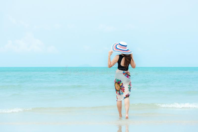 Summer Holiday. Lifestyle woman chill holding big white hat and wearing bikini fashion summer trips walking on the sandy ocean bea. Ch. Happy woman enjoy and stock image