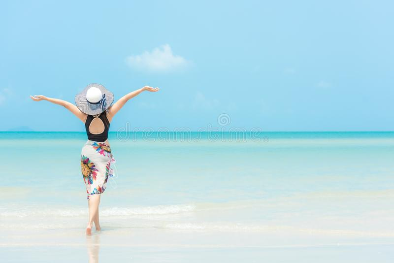 Summer Holiday. Lifestyle woman chill holding big white hat and wearing bikini fashion summer trips walking on the sandy ocean bea. Ch. Happy woman enjoy and royalty free stock photo