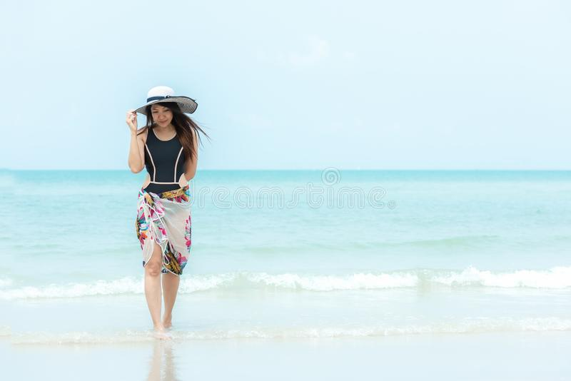 Summer Holiday. Lifestyle woman chill holding big white hat and wearing bikini fashion summer trips walking on the sandy ocean bea. Ch. Happy woman enjoy and stock images