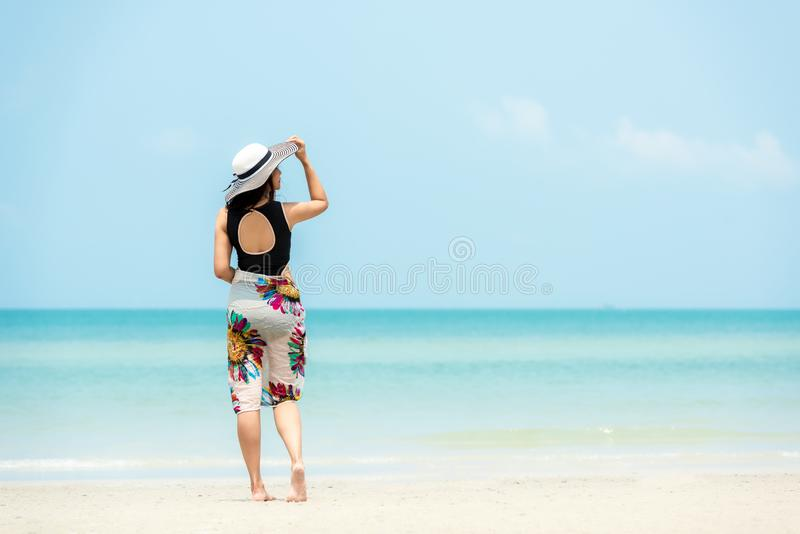 Summer Holiday. Lifestyle woman chill holding big white hat and wearing dress fashion summer trips standing chill on the sandy oce stock photography