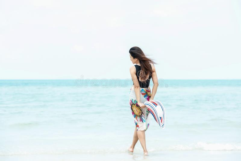 Summer Holiday. Lifestyle woman chill holding big white hat and wearing fashion summer trips walking on the sandy ocean beach. royalty free stock images