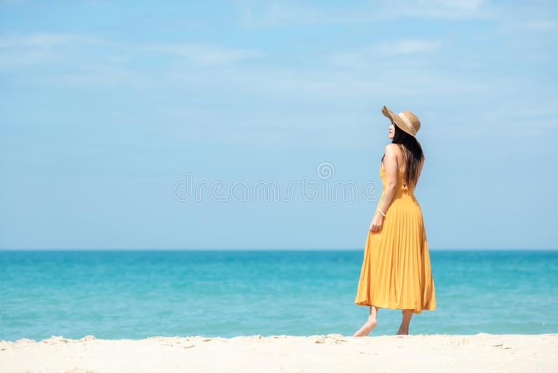 Summer Holiday. Lifestyle woman chill with yellow wearing dress fashion summer trips standing chill on the sandy ocean beach. stock images