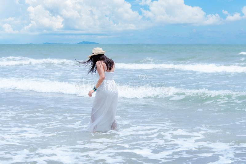Summer Holiday. Lifestyle woman white dress wearing fashion summer trips walking on the sandy ocean beach. Happy woman enjoy and r. Elax vacation. Lifestyle and stock image
