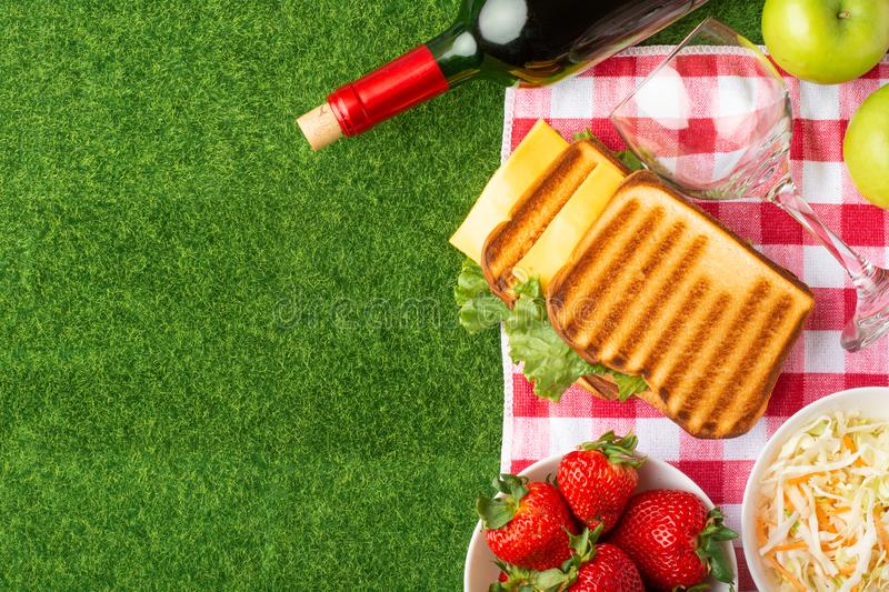 Summer holiday, Picnic in the park on the grass. Cloth, senviches, fruits, wine with glasses, top view, Flat lay, The concept of a royalty free stock image