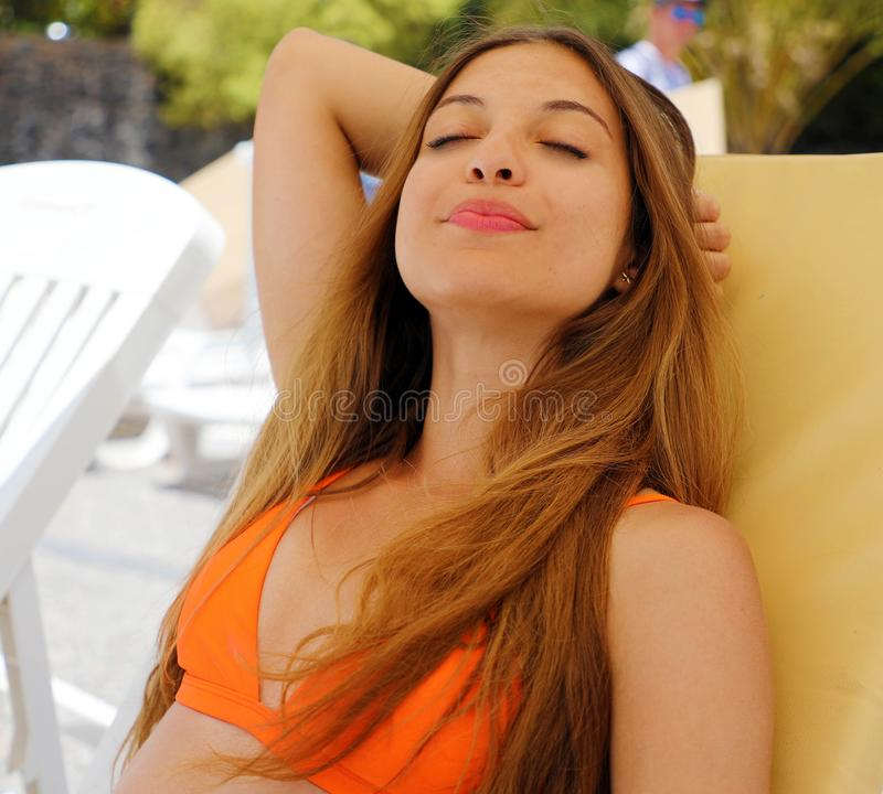 Summer holiday relax. Sexy bikini woman relax and taking a nap near swimming pool resort outdoors the hotel royalty free stock image
