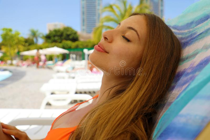Summer holiday relax. Sexy bikini woman relax and taking a nap near swimming pool resort outdoors the hotel stock images