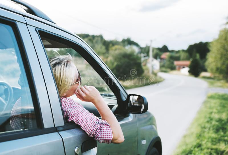Summer holiday roadtrip travel to countryside. Young hipster blond woman driving car on rural road and having fun summer vacation royalty free stock photography