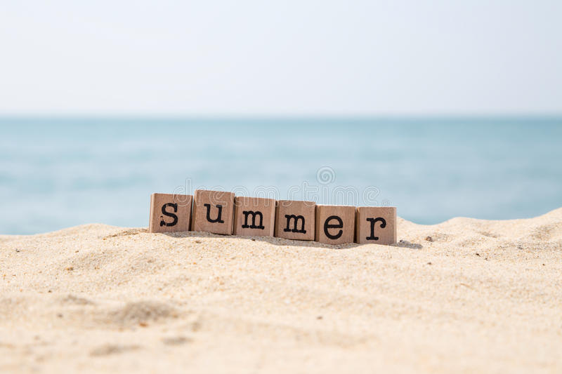 Summer holiday season at sea beach. Summer word on wood rubber stamps stack on the sand beach for holiday season concepts, beautiful blue sea view during daytime royalty free stock image