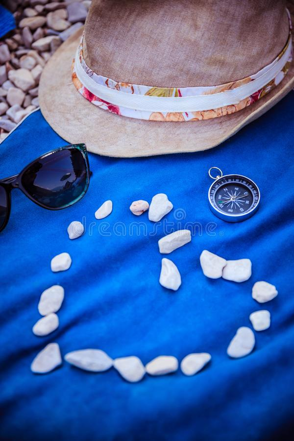 Summer holiday vacation accessories on beach, heart out of stones stock photo