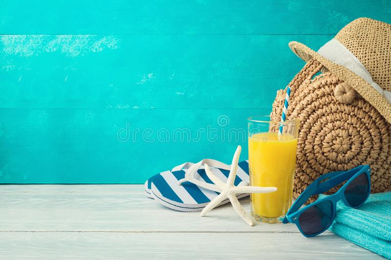 Summer holiday vacation background with orange juice, beach fashion bag and flip flops royalty free stock photo