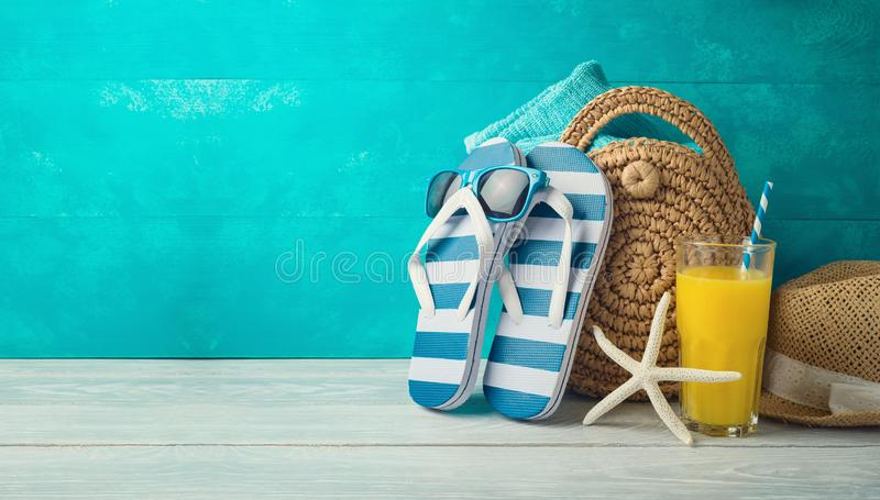Summer holiday vacation background with orange juice, beach fashion bag and flip flops. On wooden table royalty free stock photography