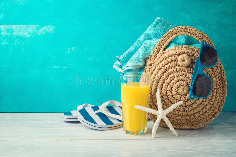 Summer holiday vacation background with orange juice, beach fashion bag and flip flops. On wooden table royalty free stock photos