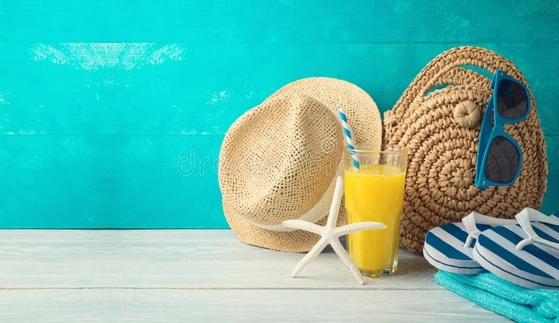 Summer holiday vacation background with orange juice, beach fashion bag and flip flops. On wooden table royalty free stock image