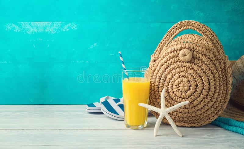 Summer holiday vacation background with orange juice, beach fashion bag and flip flops. On wooden table royalty free stock images