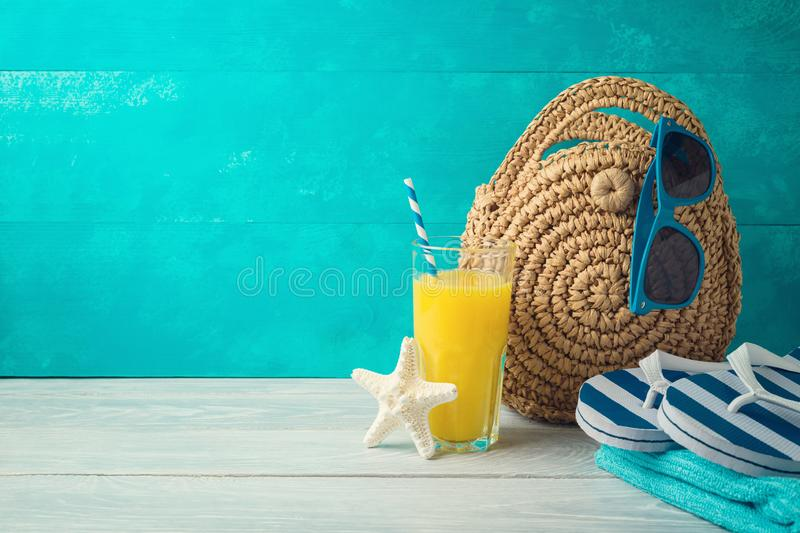 Summer holiday vacation background with orange juice, beach fashion bag and flip flops. On wooden table stock images