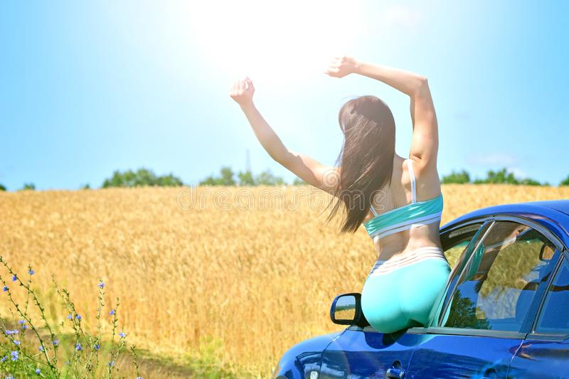 Summer holiday and vacation concept. Sporty pretty girl leaned out of the car window and enjoys the summer landscape and weather. stock photo