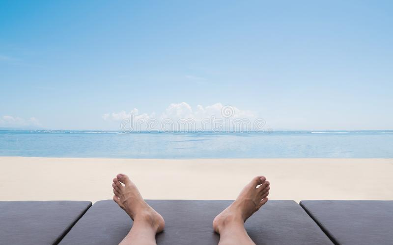 Summer holiday and vacation. a man relaxing on sunbathing lounge chair on the beach in summer stock photo