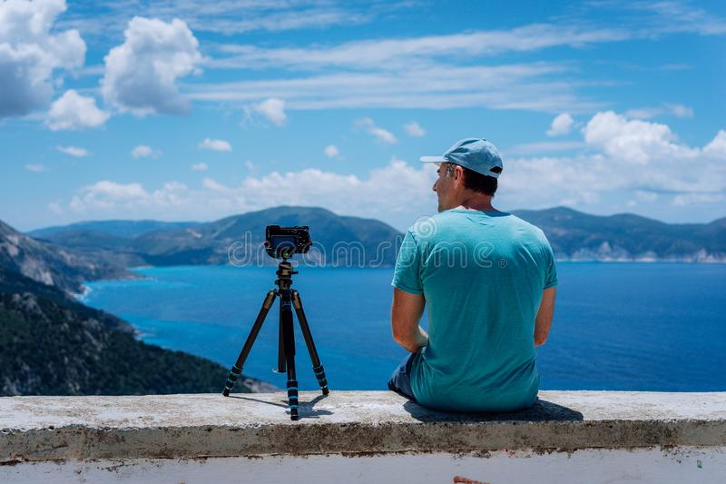Summer holiday visiting Greece. Male freelance photographer enjoying capturing time lapse moving cloudscape coastline royalty free stock image
