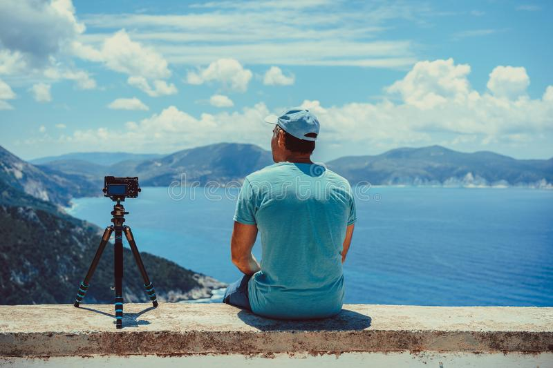 Summer holiday vocation visiting Greece. Male photographer enjoying capture time lapse moving cloudscape coastline and stock photos