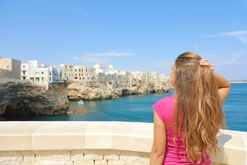 Summer holidays in Apulia. Back view of beautiful young woman enjoying Polignano a mare view, Mediterranean Sea, Italy royalty free stock photo