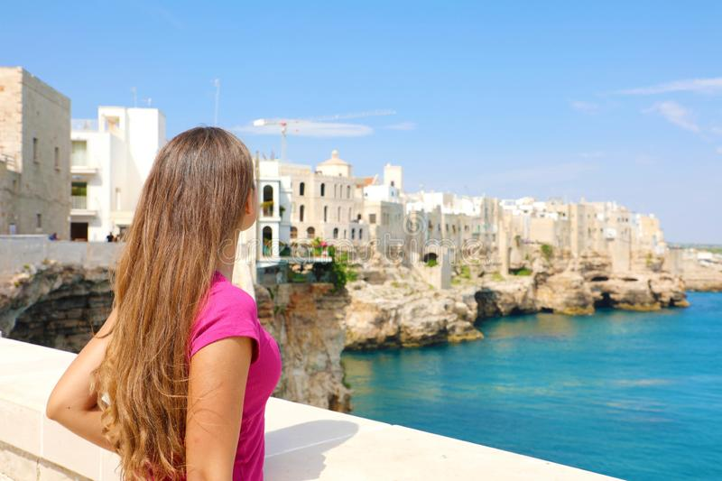 Summer holidays in Apulia. Back view of beautiful young woman in Polignano a mare town on Mediterranean Sea, Italy royalty free stock photos