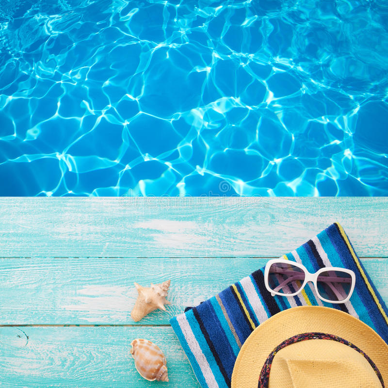 Summer Holidays in Beach Seashore. Fashion accessories summer flip flops, hat, sunglasses on bright turquoise board near the pool stock photos
