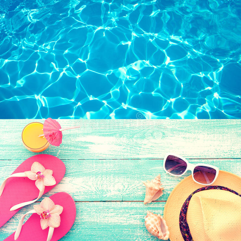 Summer Holidays in Beach Seashore. Fashion accessories summer flip flops, hat, sunglasses on bright turquoise board near the pool. Summer Holidays in Beach stock images