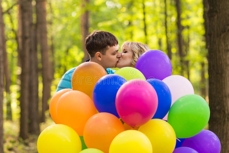 Summer holidays, celebration and dating concept - couple with colorful balloons outdoors royalty free stock images